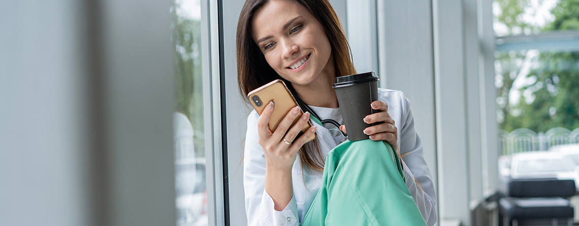 Nurse looking at smartphone smiling while holding a to-go cup of coffee - Verizon discount for nurses