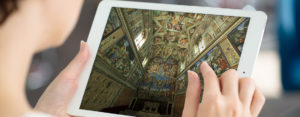 woman holding iPad while view a virtual tour of the Sistine Chapel