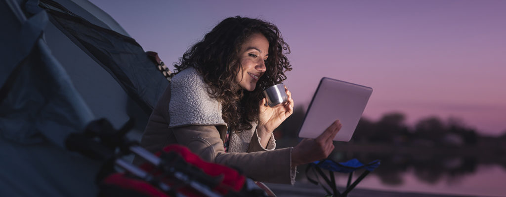 woman sipping drink from cup in a tent while streaming a show on her iPad