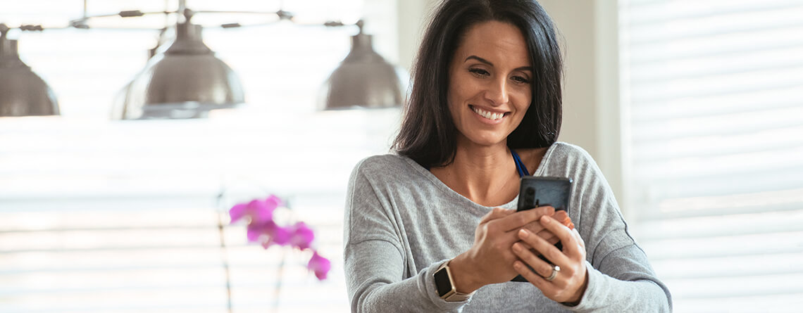 woman looking at smartphone in kitchen