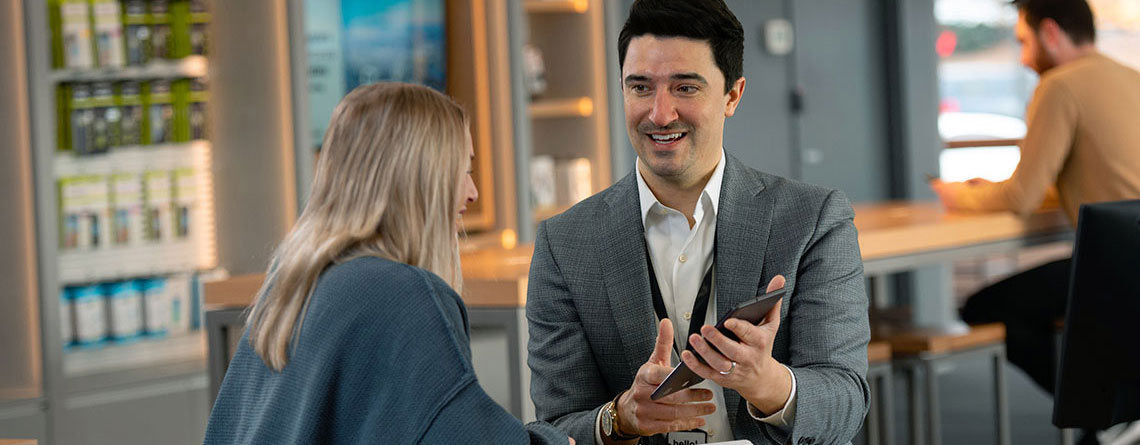 cellular sales wireless sales consultant helping woman in store shopping for a new smartphone