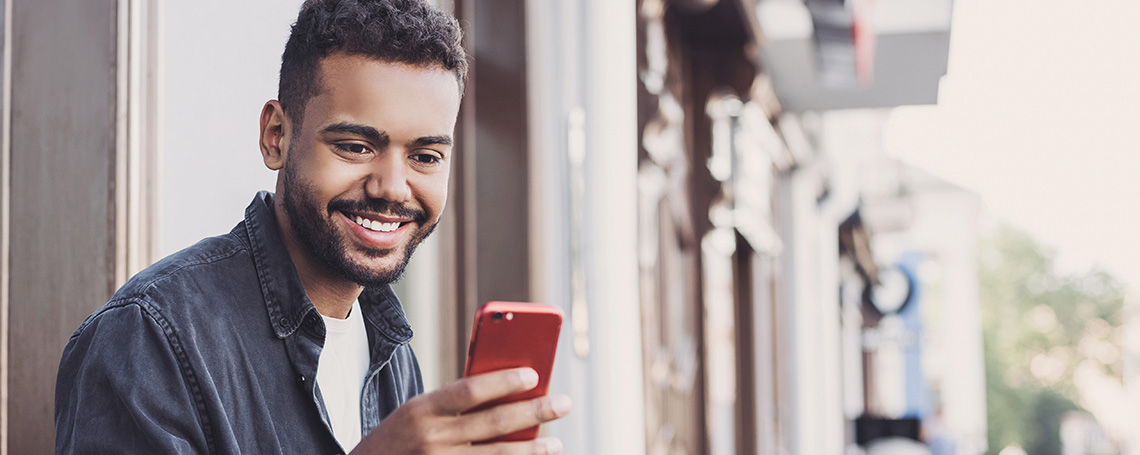 man checking passive income on red smartphone outside