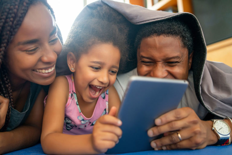 family laughing while watching show on tablet